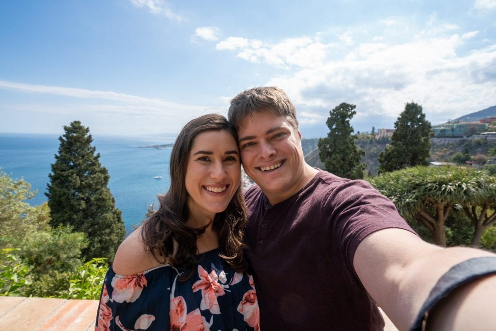 Selfie of Kate and Jeremy in Taormina Sicily. You can see the sea in the background.
