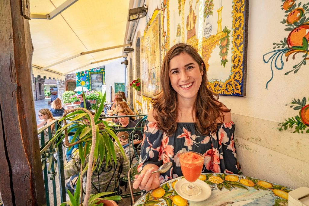 Kate Storm sitting a table at BamBar in Taormina. There's an orange granita in front of her and yellow tile work behind her. Visiting BamBar is absolutely one of the best things to do in Taormina Sicily!