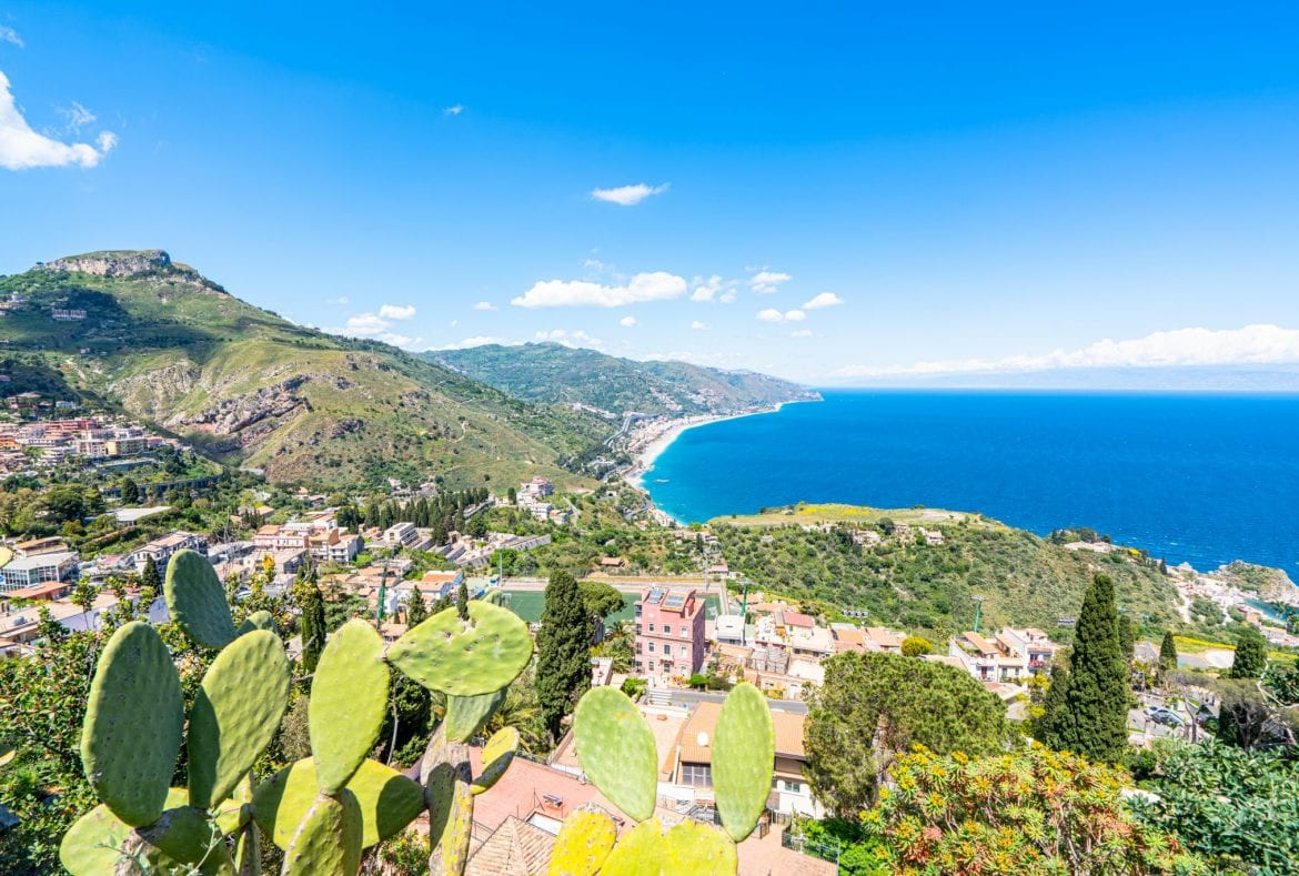 Photo of the Ionian Sea as seen from Taormina. There are cacti in the foreground of the photo.