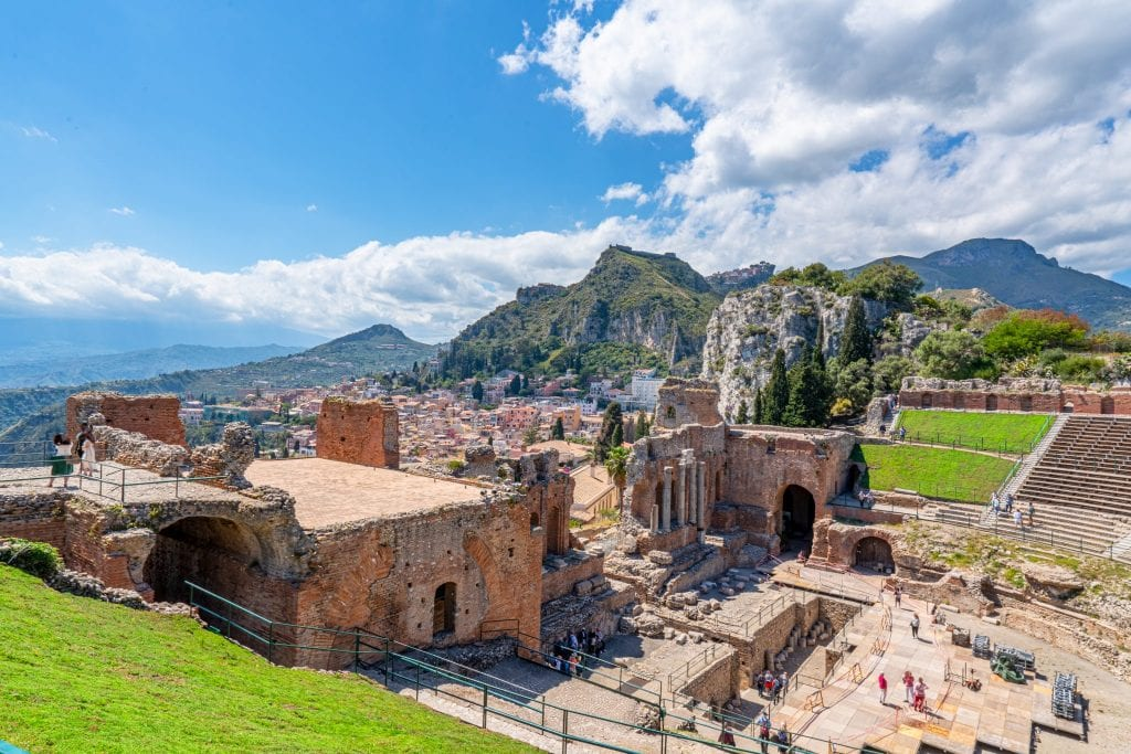 Photo of Taormina visible beyond part of the Greek Theatre.