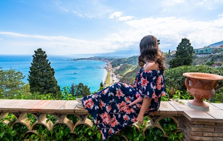 Kate Storm in a floral dress sitting on a garden wall overlooking the sea in Taormina Sicily