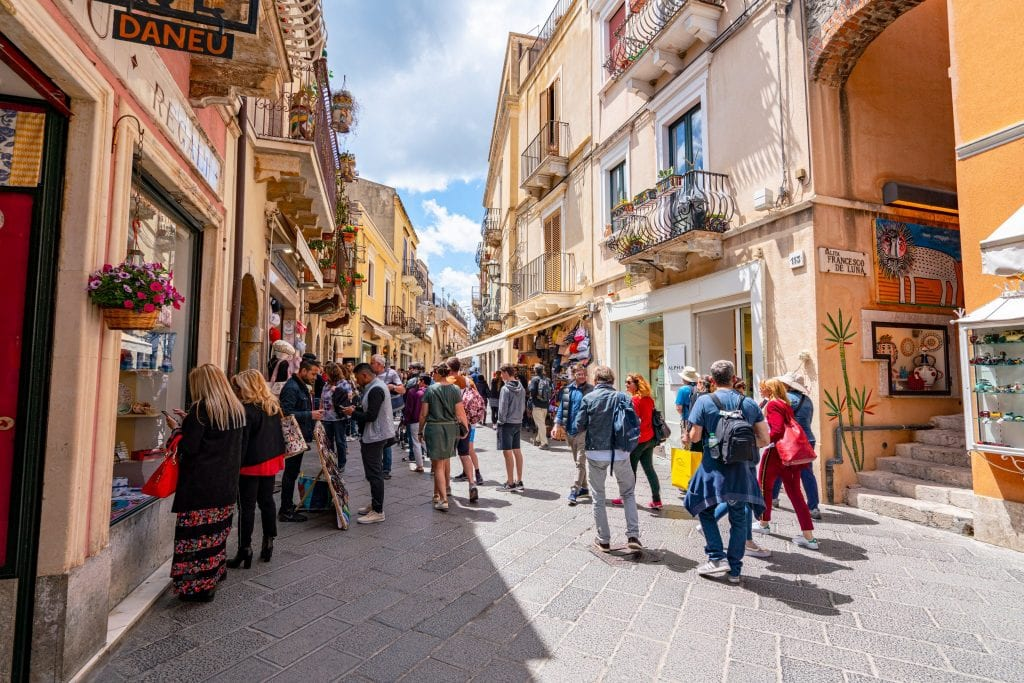 Photo of Corso Umberto in Taormina Sicily. There's a crowd of people in the street.