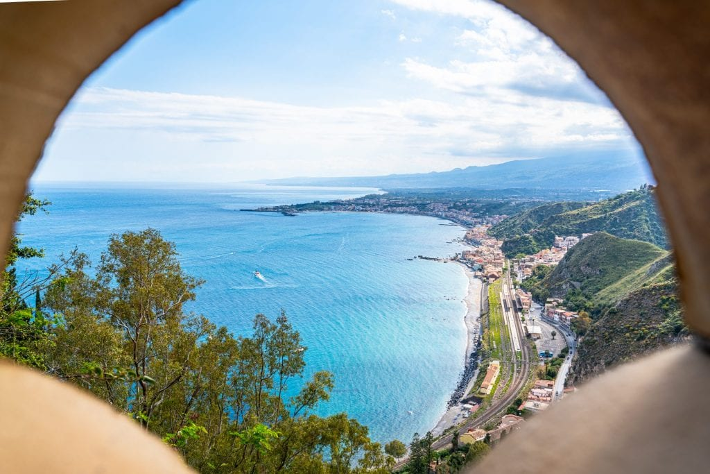 View of a beach along the Ionian Sea as seen by peaking through a gate at Villa Comunale, one of the best places to visit in Taormina Sicily!