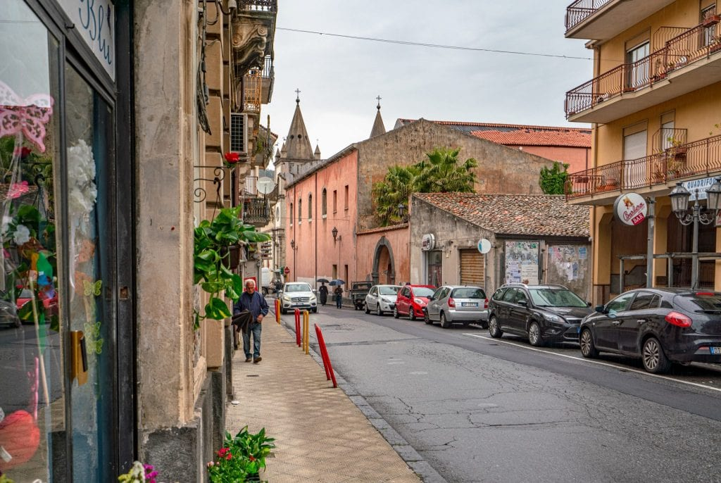 Quiet street in Francavilla Sicily on a rainy day with cars parked along the edge