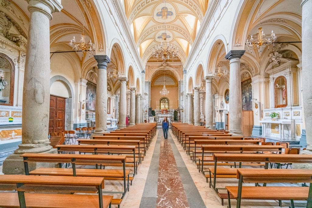Kate Storm in a blue shirt standing in a church in Francavilla Sicily