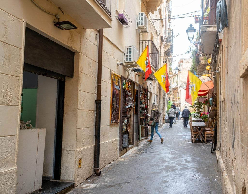 small street in Syracuse Sicily with flags outside the shop windows