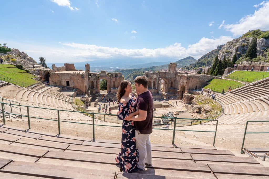 Kate and Jeremy standing in Greek Theatre in Taormina--visiting this place is easily one of the best things to do in Taormina! Kate and Jeremy are facing each other, Kate is wearing a floral maxi dress.