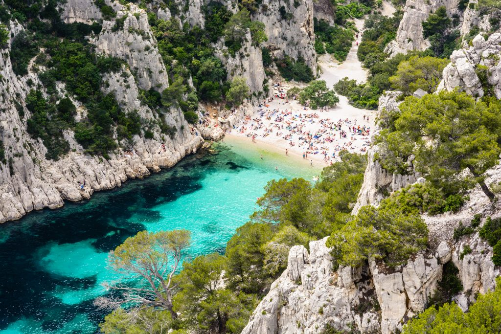 crowded beach at a french calanque as seen from above