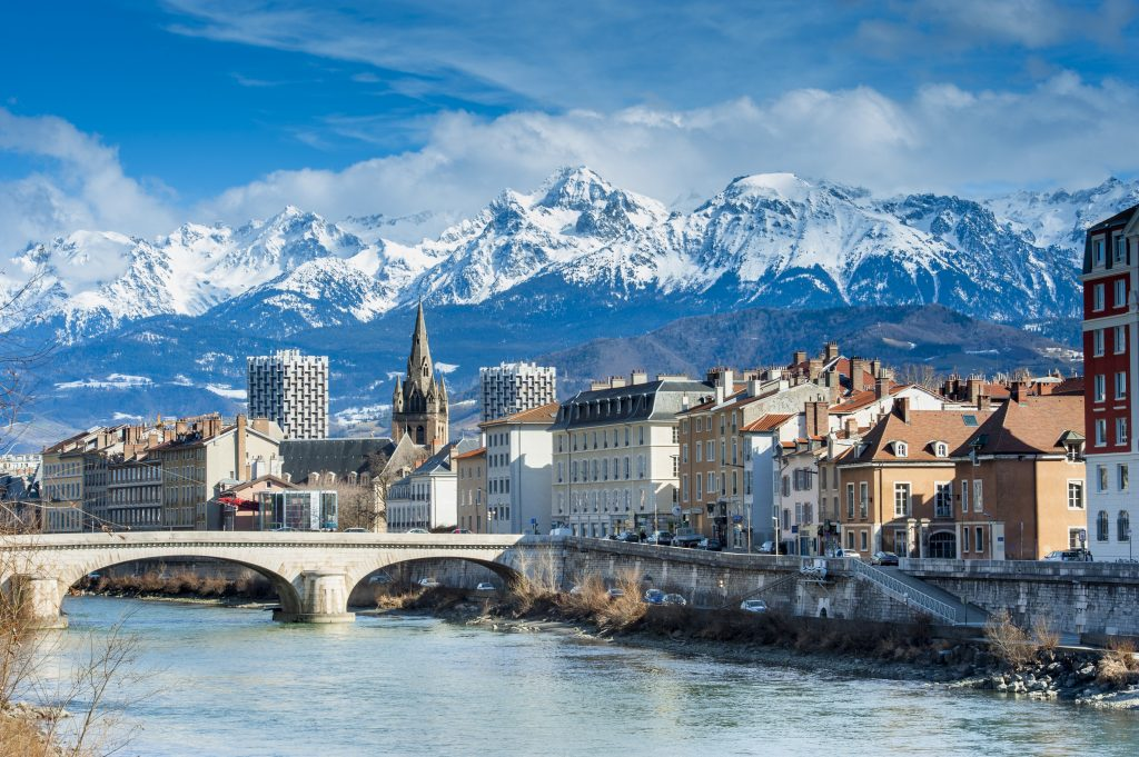city of grenoble france with river in the foreground and snowcapped mountains in the background