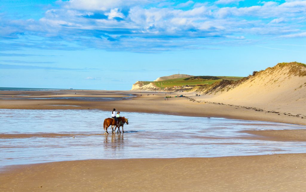 two people riding horses on a sandy stretch of the opal coast in northern france road trip