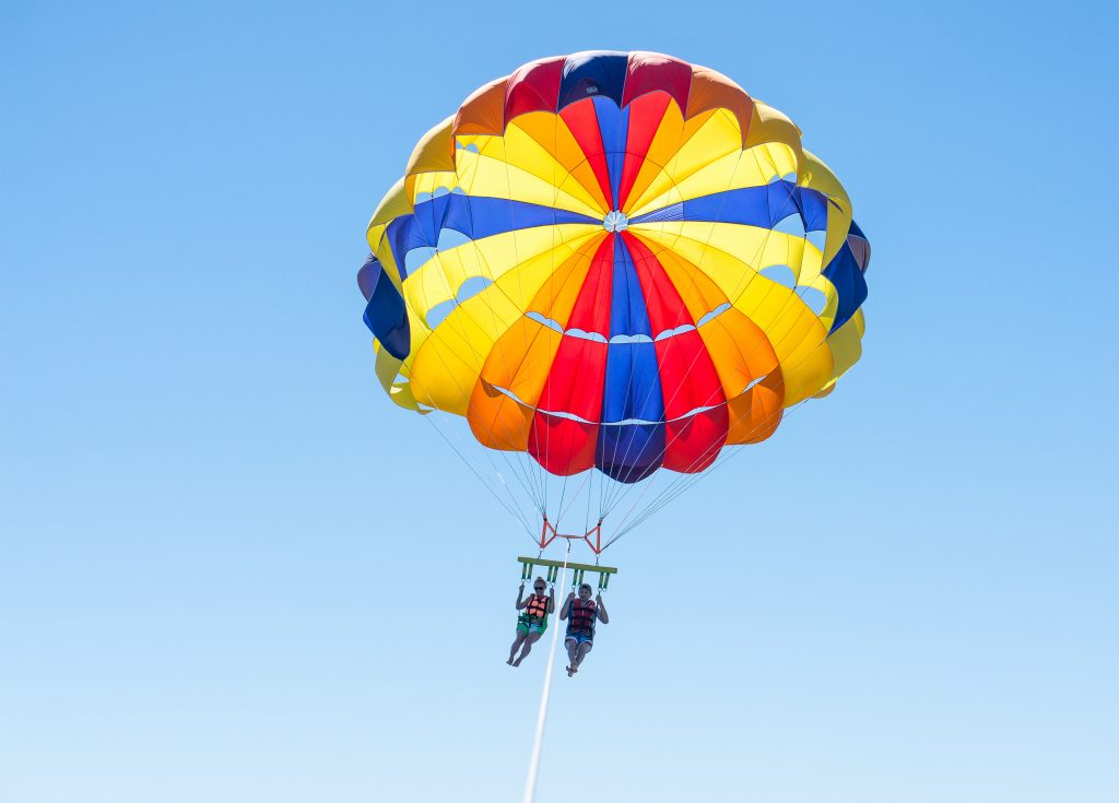 two people parasailing in a multi colored parasail
