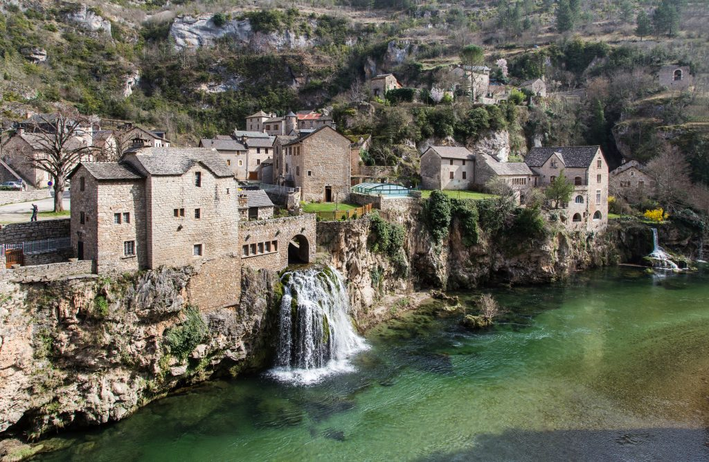 village is gorges du tarn france with a waterfall spilling into the river