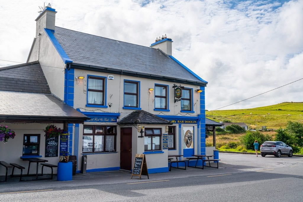 Exterior McDermott's Pub in Doolin. The building is white with blue trim.