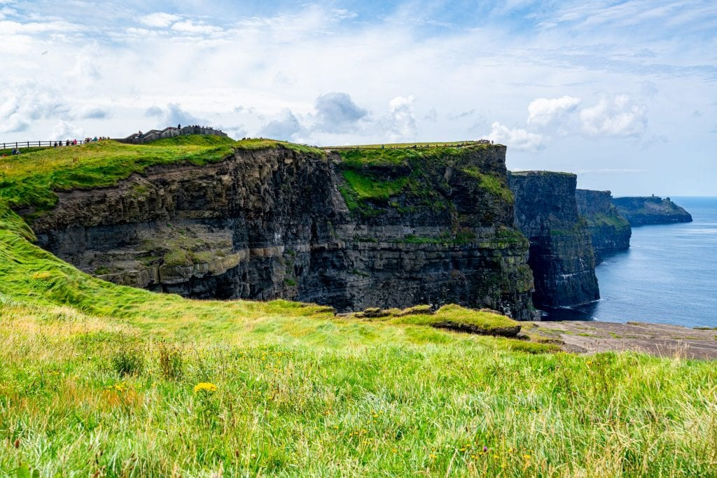 Cliffs of Moher in Ireland visible beyond a patch of bright green grass