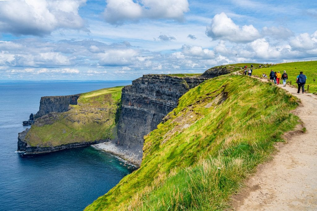 People hiking along the Cliffs of Moher Coastal Walk near Doolin Ireland, a small beach is visible on the left