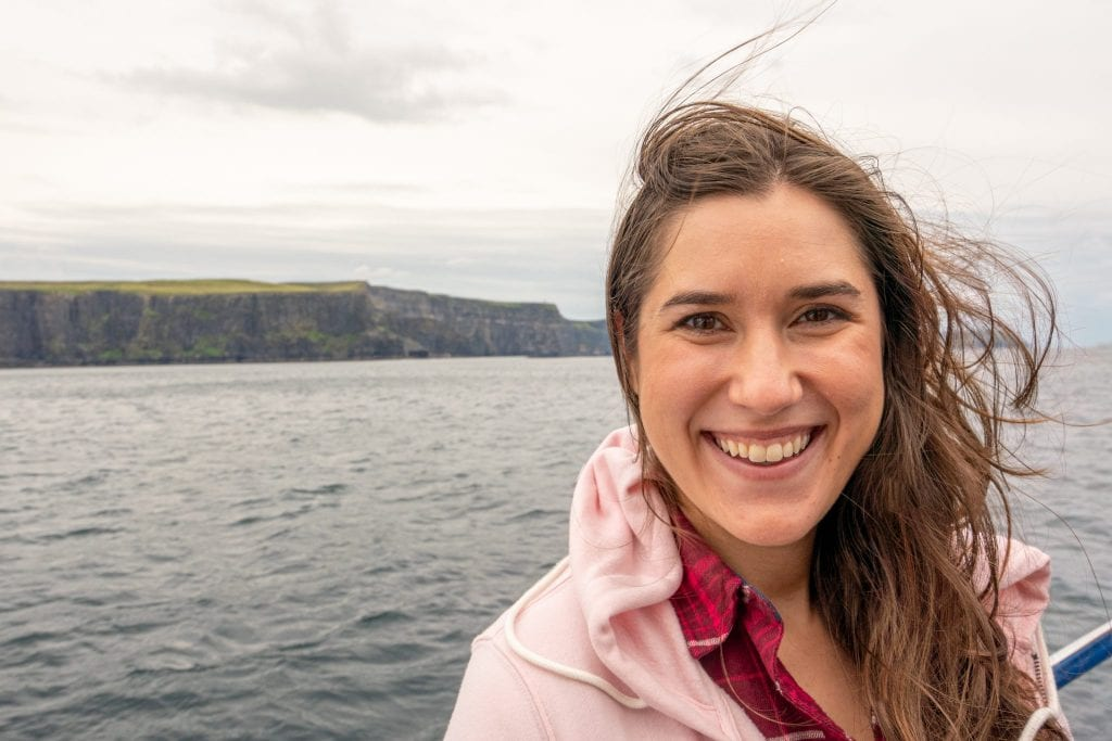 Kate Storm wearing a pink jacket and smiling at the camera during a Cliffs of Moher cruise--the cliffs as visible in the background.
