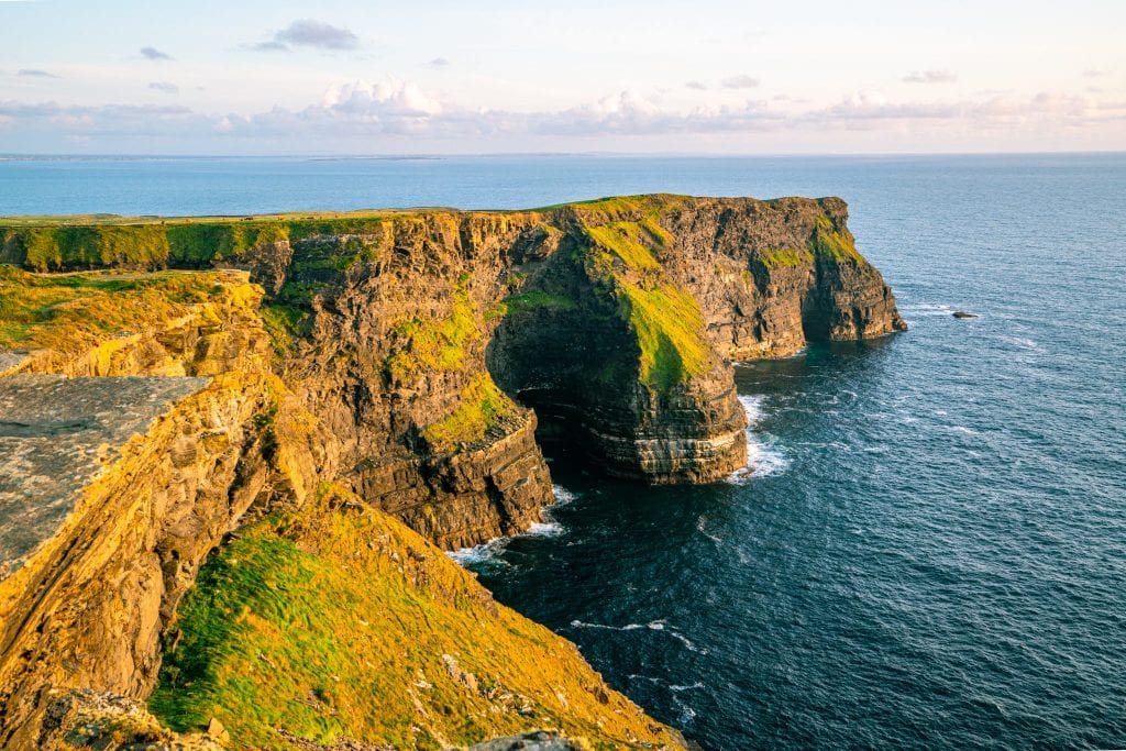 Section of the Cliffs of Moher lit up as a golden color from the sunset