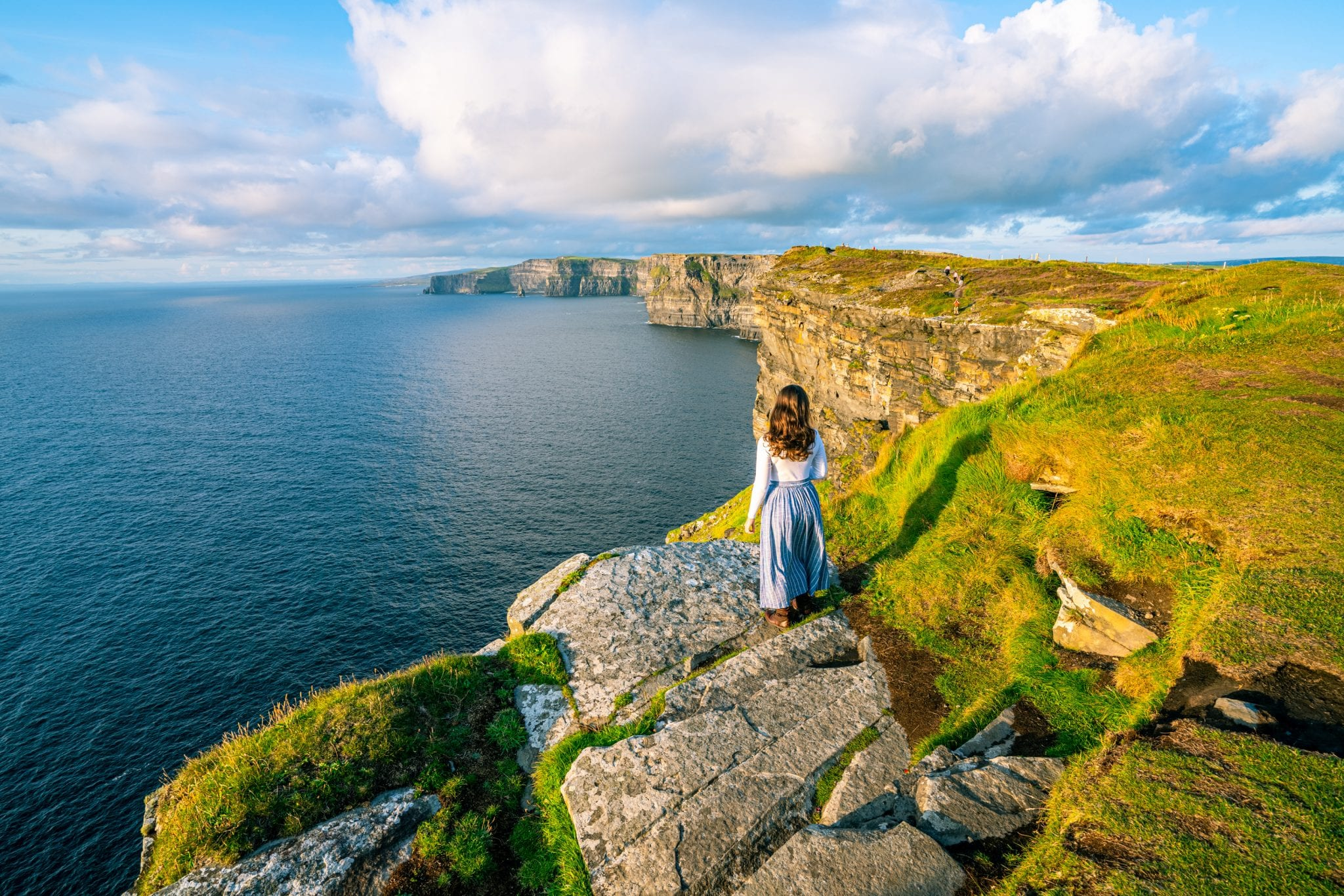 Kate Storm in a blue skirt standing in front of the Cliffs of Moher in Ireland. She's looking away from the camera.