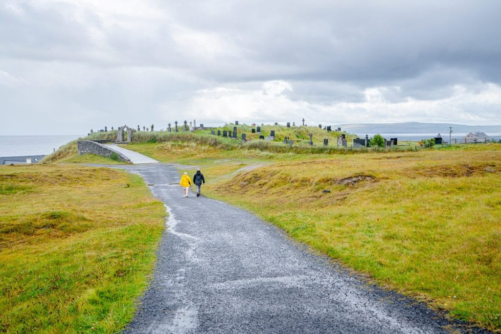 Couple in the distance walking down an empty road on Inisheer Island that leads to a small cemetery