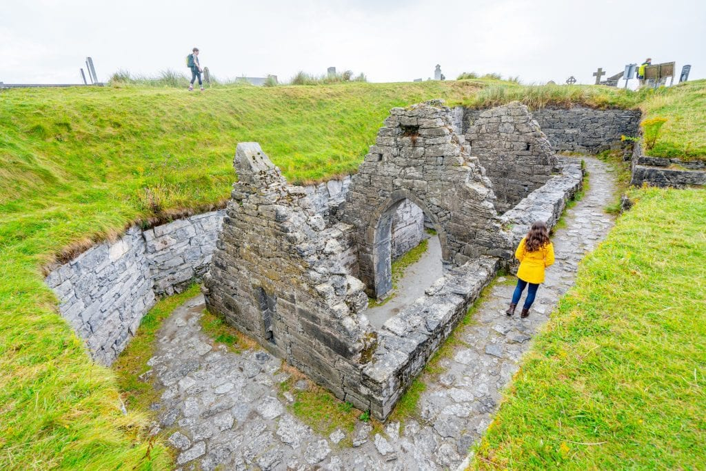 Kate Storm in a yellow raincoat walking along the edge of the sunken church on Inisheer Ireland