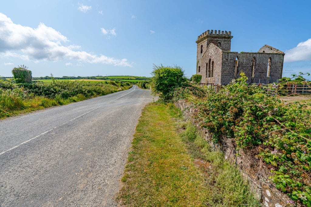 Empty road with castle to the right as seen on the Hook Peninsula, one of the best day trips from Dublin Ireland