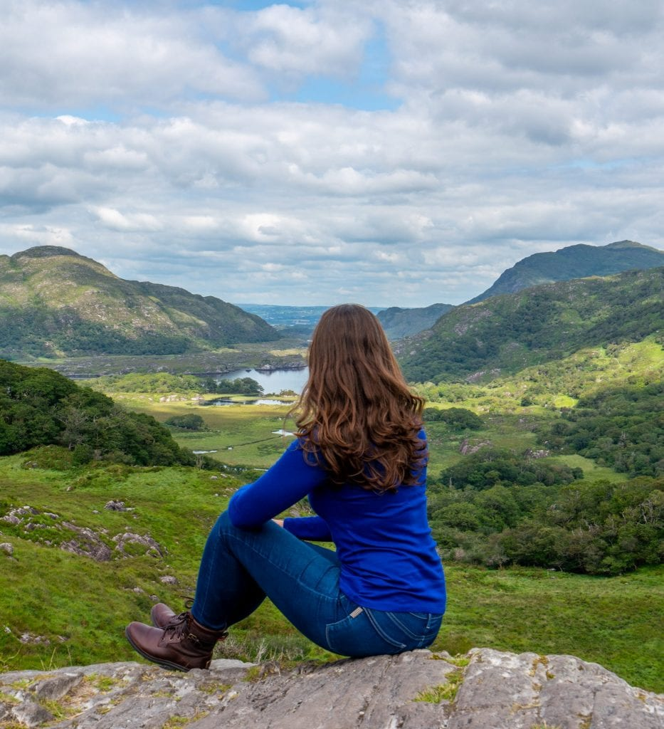 Kate Storm overlooking Ladies View in Killarney National Park, wearing a blue shirt and looking away from the camera. Views like this are perfect for visiting during your honeymoon in Ireland!
