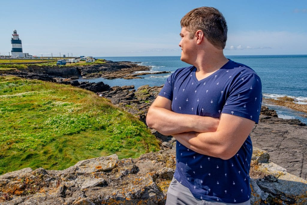 Jeremy Storm in a blue shirt looking at Hook Lighthouse in County Wexford Ireland