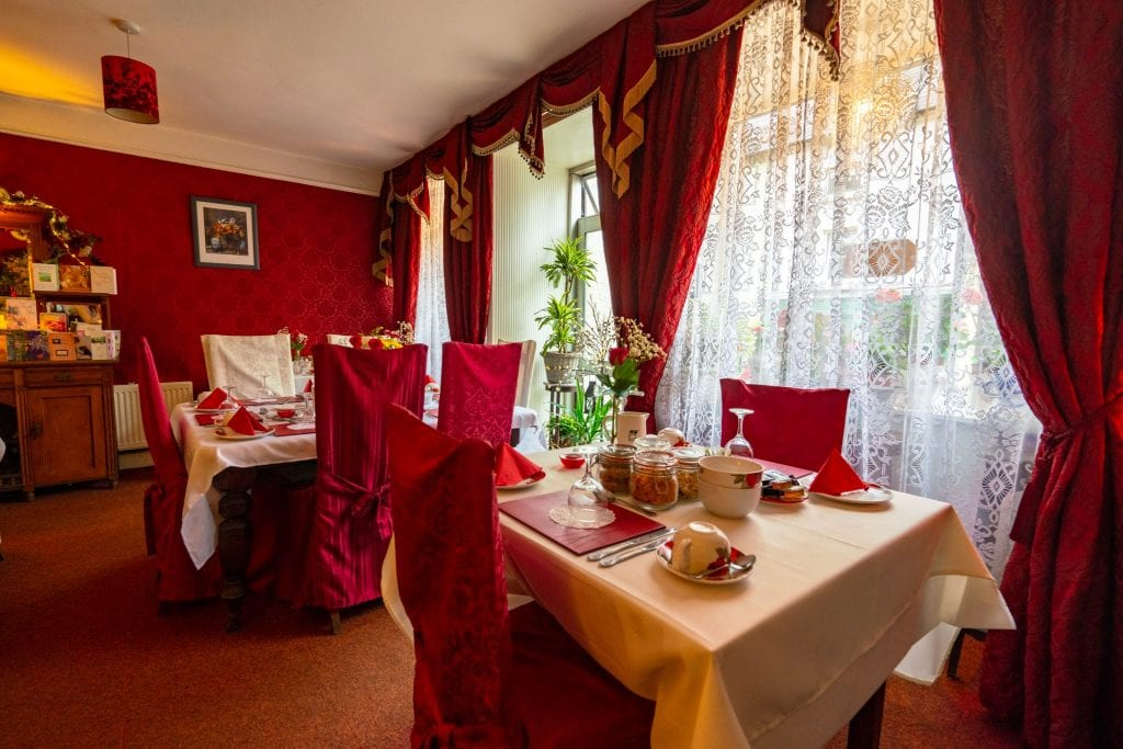 Breakfast room at Inishross House with red chairs and red curtains--definitely a cozy place to stay as part of your honeymoon in Ireland!