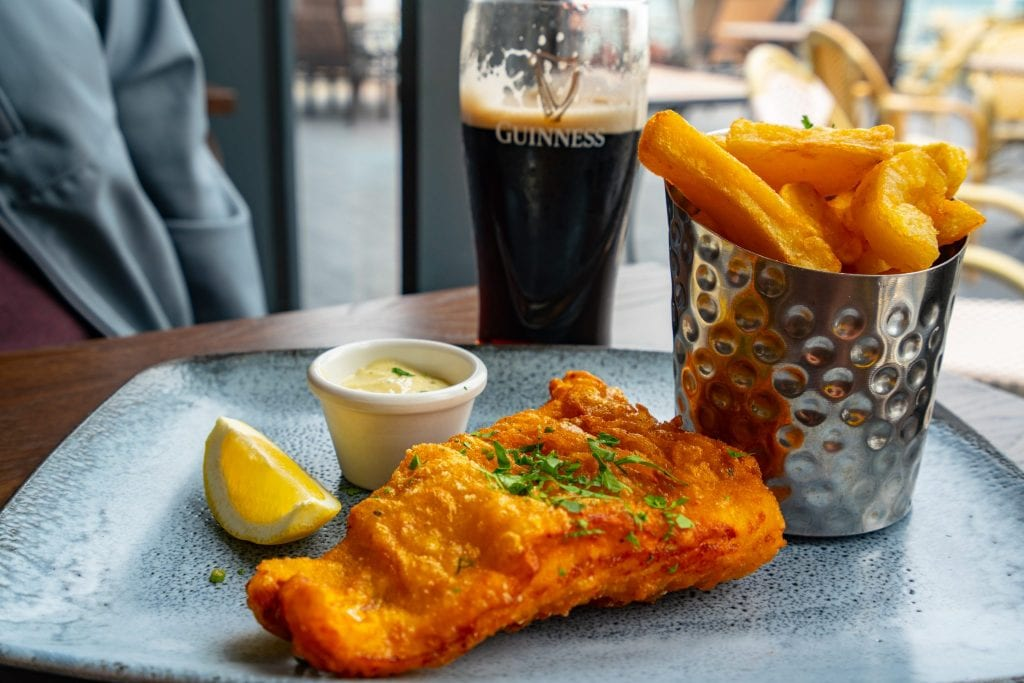 Plate of fish and chips in Ireland with a glass of Guinness in the background--a traditional Irish food meal