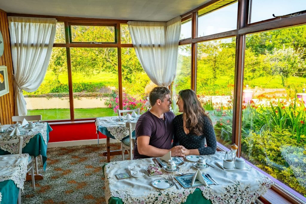 Jeremy Storm and Kate Storm at a breakfast table in Find Us Farmhosue, an excellent bed and breakfast getaway to consider during your Ireland honeymoon!