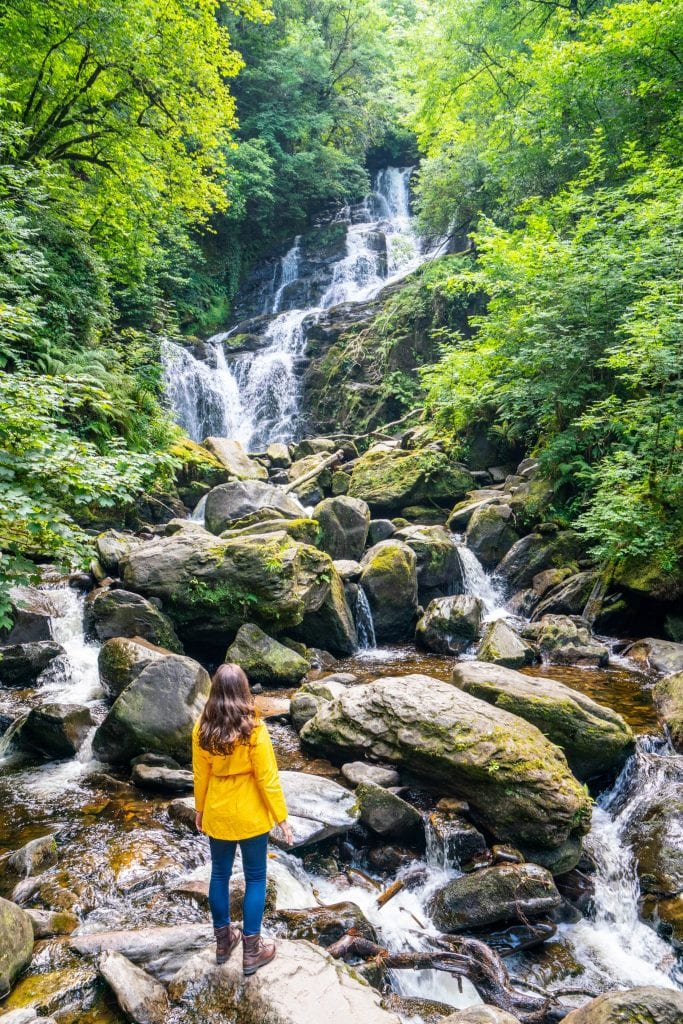 Kate Storm in a yellow raincoat standing in front of Torc Waterfall in Killarney National Park Ireland