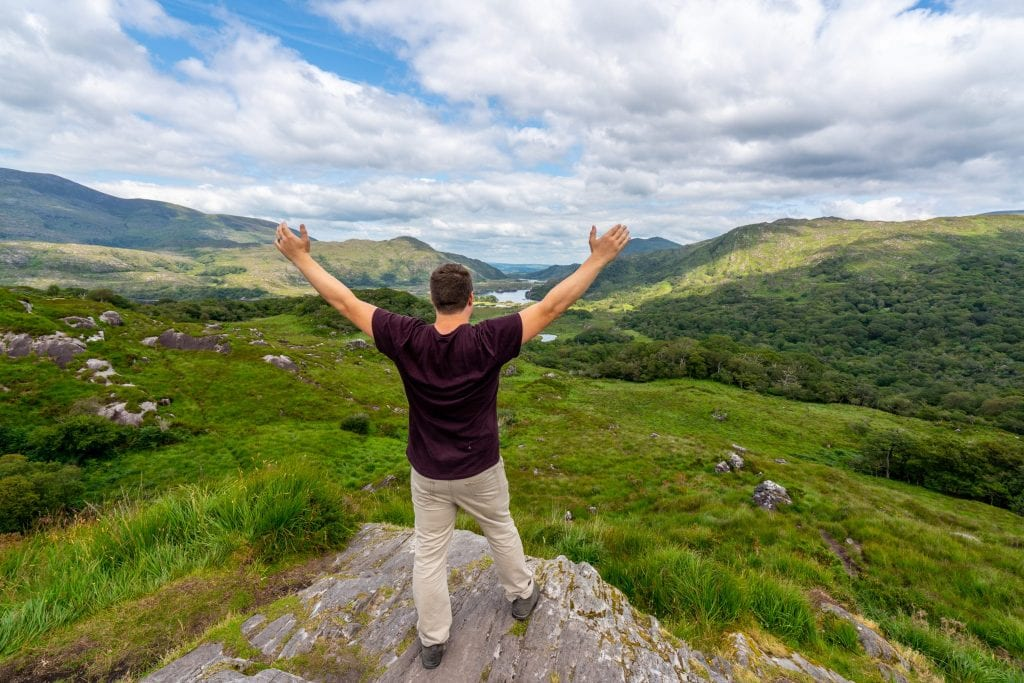 Jeremy Storm standing at an overlook in Killarney National Park, facing away from the camera with his arms in the air.