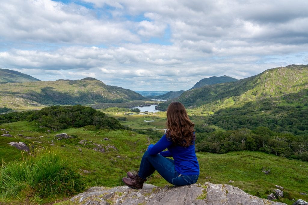 Kate Storm in a blue long-sleeved shirt overlooking Killarney Natoinal Park--a must-see spot when planning a trip to Ireland!