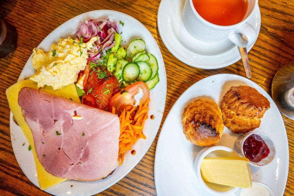 Open-faced ham sandwich shot from above with a plate of scones and cup of tea next to it
