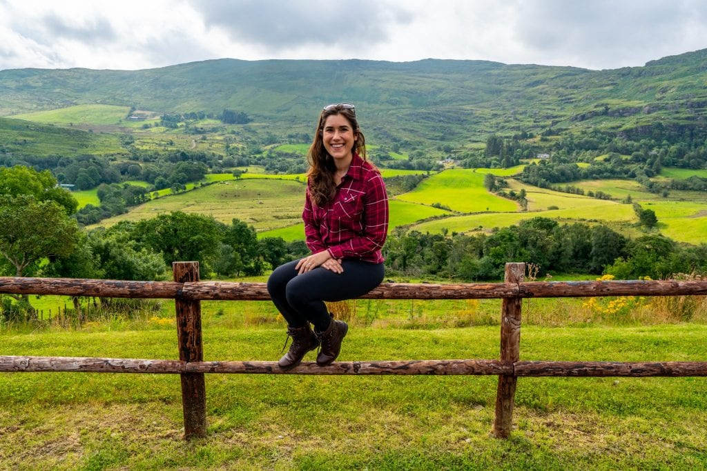 Kate Storm sitting on a wooden split level fence in Ireland with countryside behind her.