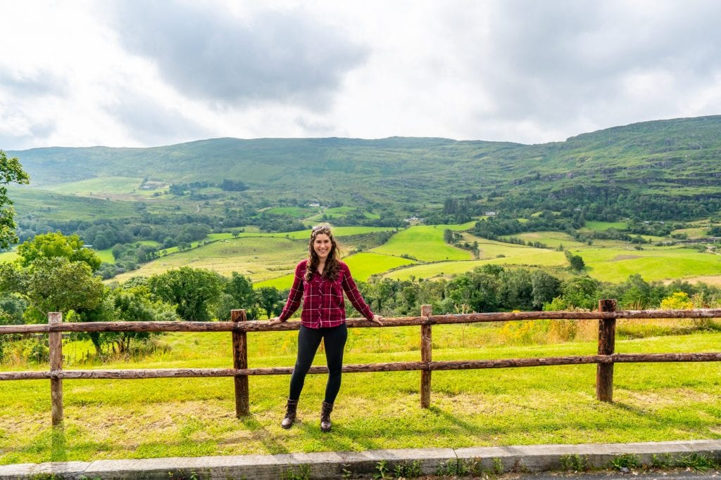 Kate Storm standing against a split level fence with Irish countyside in the background--plenty of this to be found on an Ireland road trip!