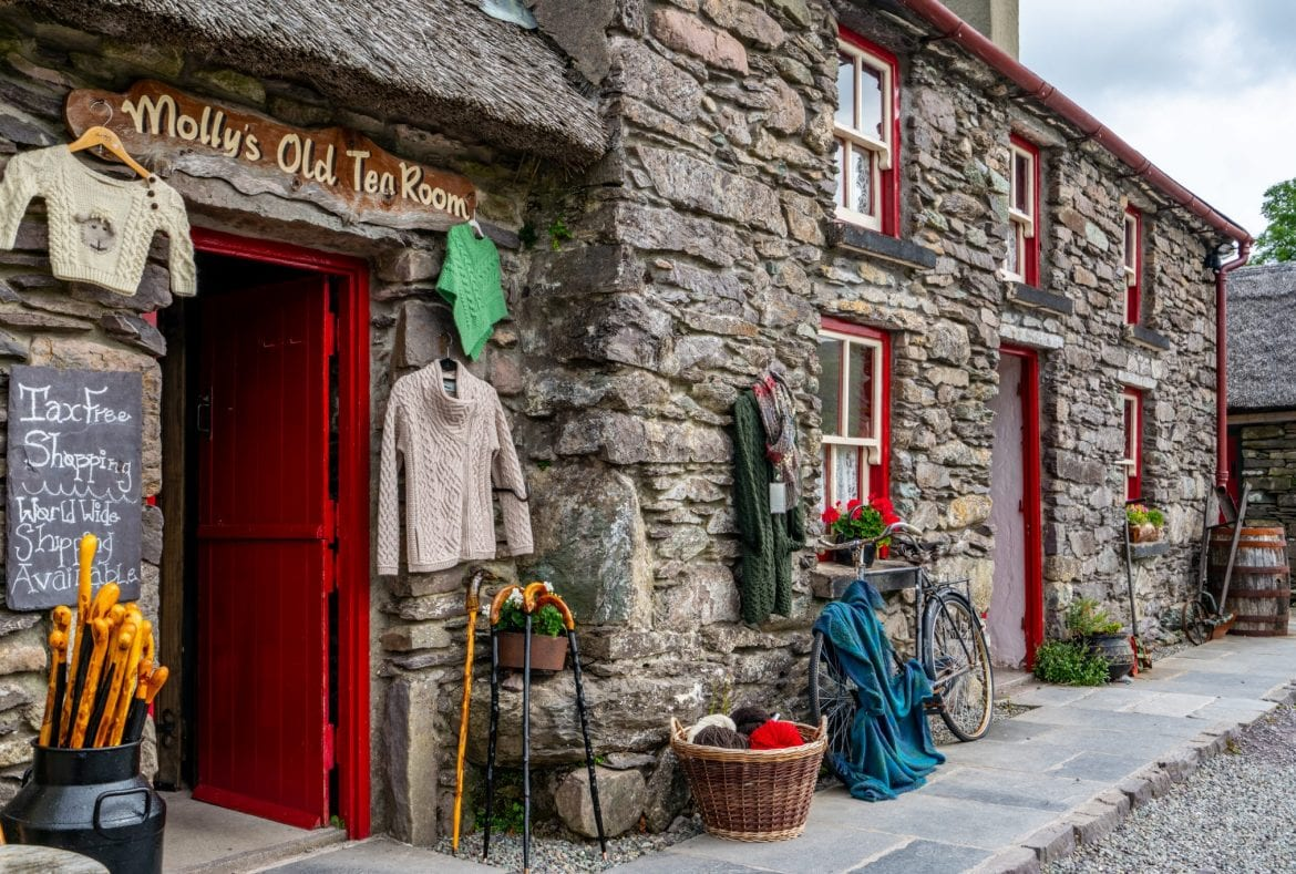 Souvenir shop in Ireland selling wool sweaters. The building is stone and red. If you want to buy wool in Ireland, don't overpack when deciding what to bring to Ireland.