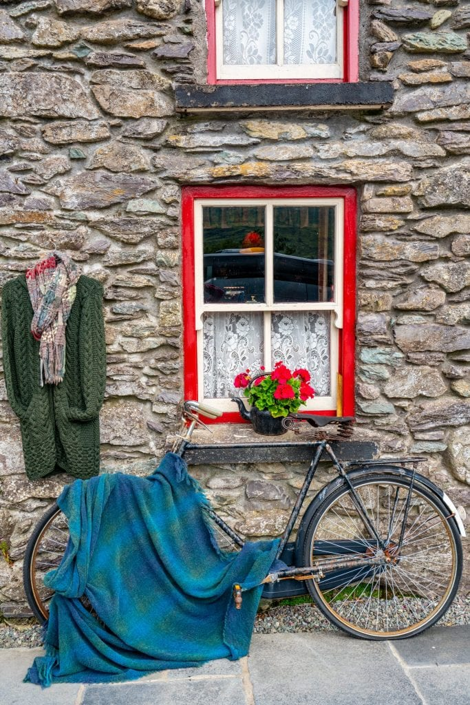 Stone building in Ireland with a bike leaning against the wall. A wool blue blanket is laying over the bike and a window in the building is lined in red