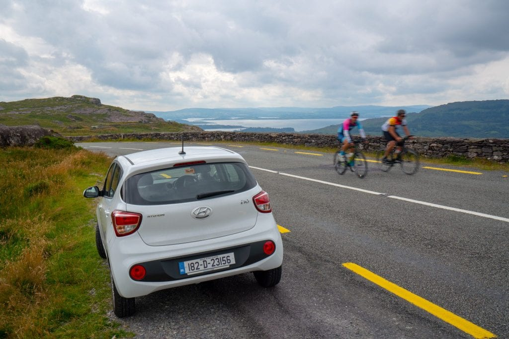 Photo of car parked on the side of the road during an Ireland road trip. Two bikers are visible passing by on the right side of the photo.
