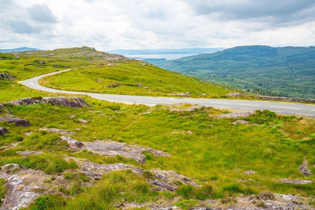 Empty curving road in Ireland with green fields on either side--it's worth making sure you have all the necessary road trip essentials before starting an epic drive out here!