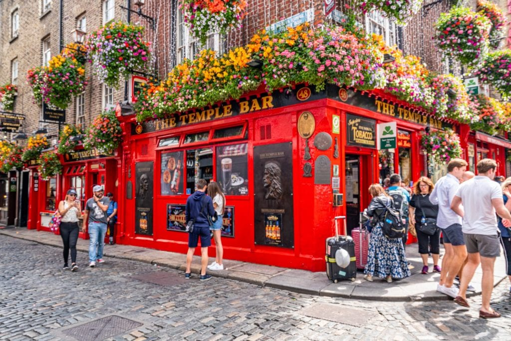 Temple Bar as seen on a summer day, with flowers over the entrance to the bar--an iconic bar, it's worth at least stopping by during a 2 day Dublin itinerary.