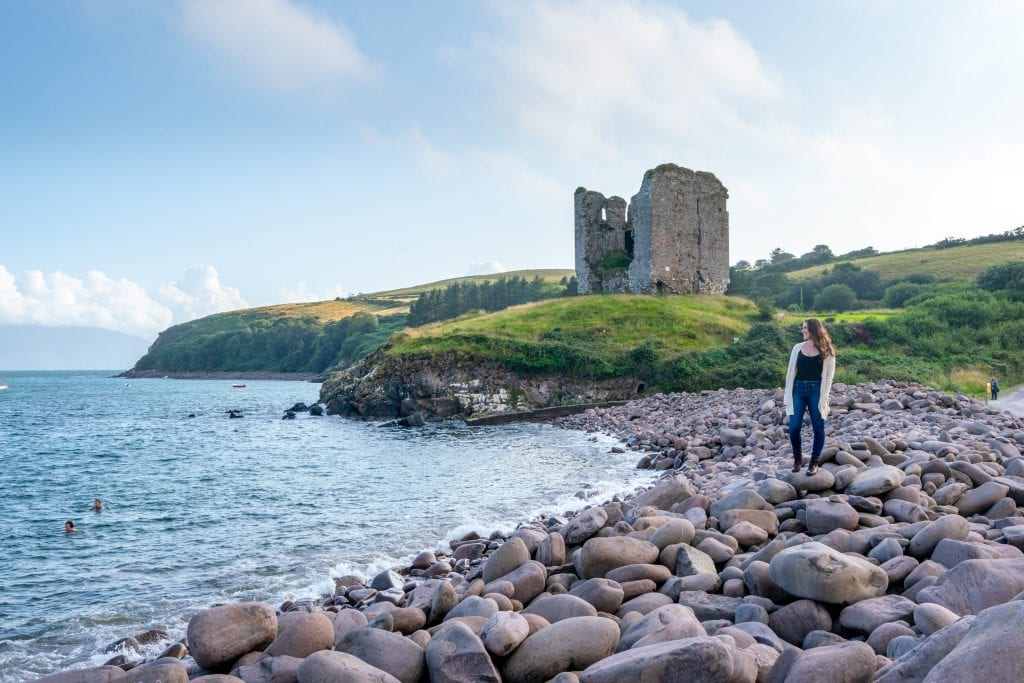 Kate Storm standing on a pebble beach on Dingle Peninsula, Ireland. Minard Castle is behind her. This is a great example of what to wear in Ireland!