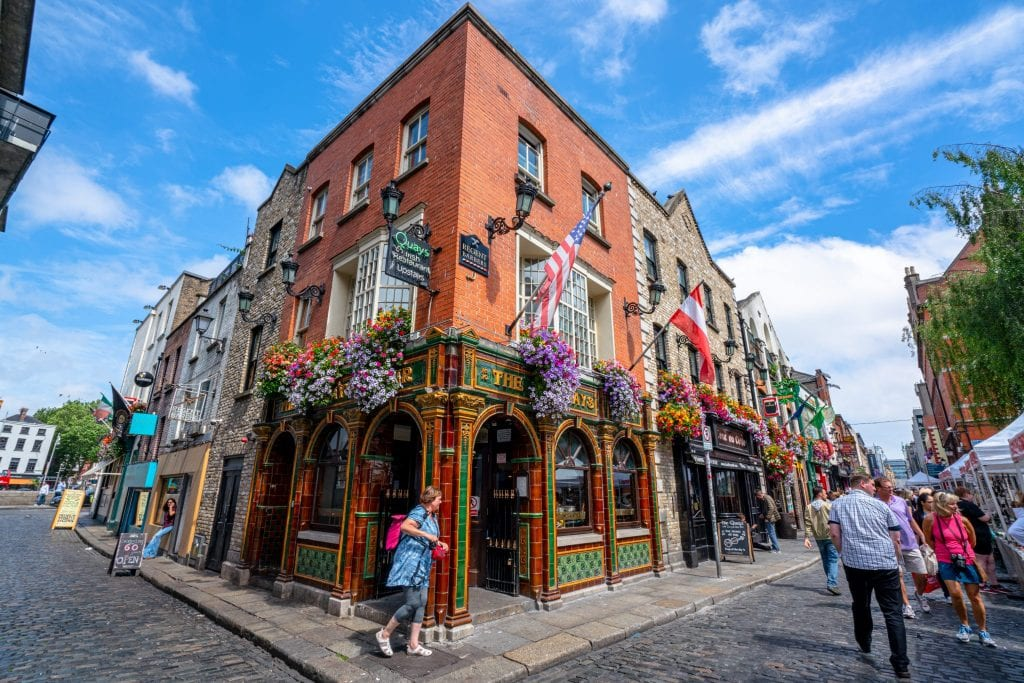 Photo of building in Dublin Ireland with flowers and flags on it. There are people walking in front of the building.