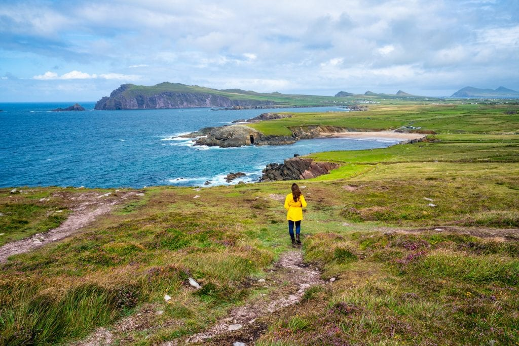 Kate Storm on Slea Head Drive on the Dingle Peninsula in Ireland, facing away from the camera and wearing a yellow raincoat.