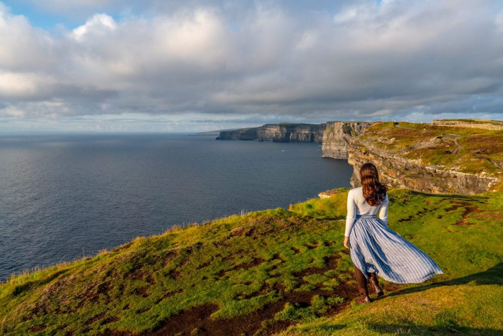 Kate Storm in a blue skirt looking away from the camera and looking out at the Cliffs of Moher--if you plan carefully, views like this won't factor into your trip to Ireland cost, because they're free!