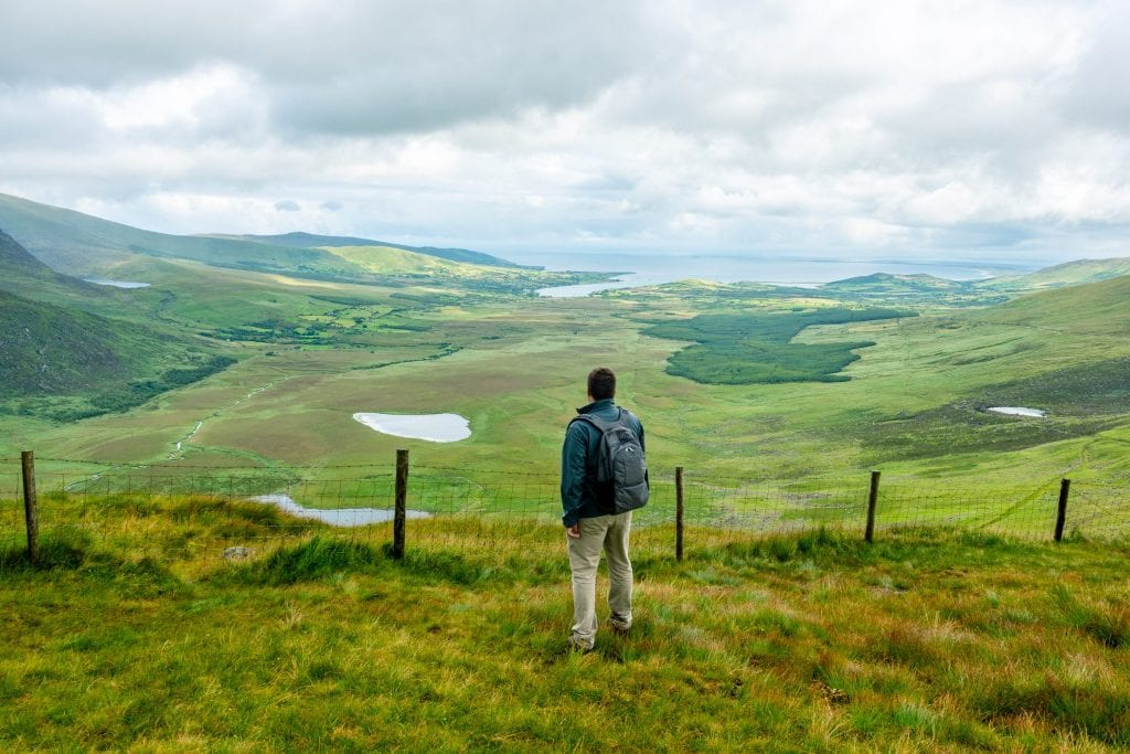 Jeremy Storm carrying a pacsafe backpack and wearing a gray jacket, looking out over Conor Pass in Ireland