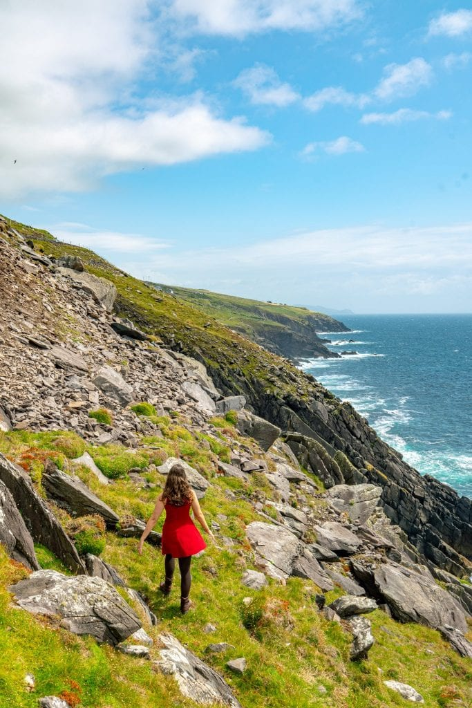 Kate Storm in a red dress walking along a cliff on Slea Head Drive Ireland