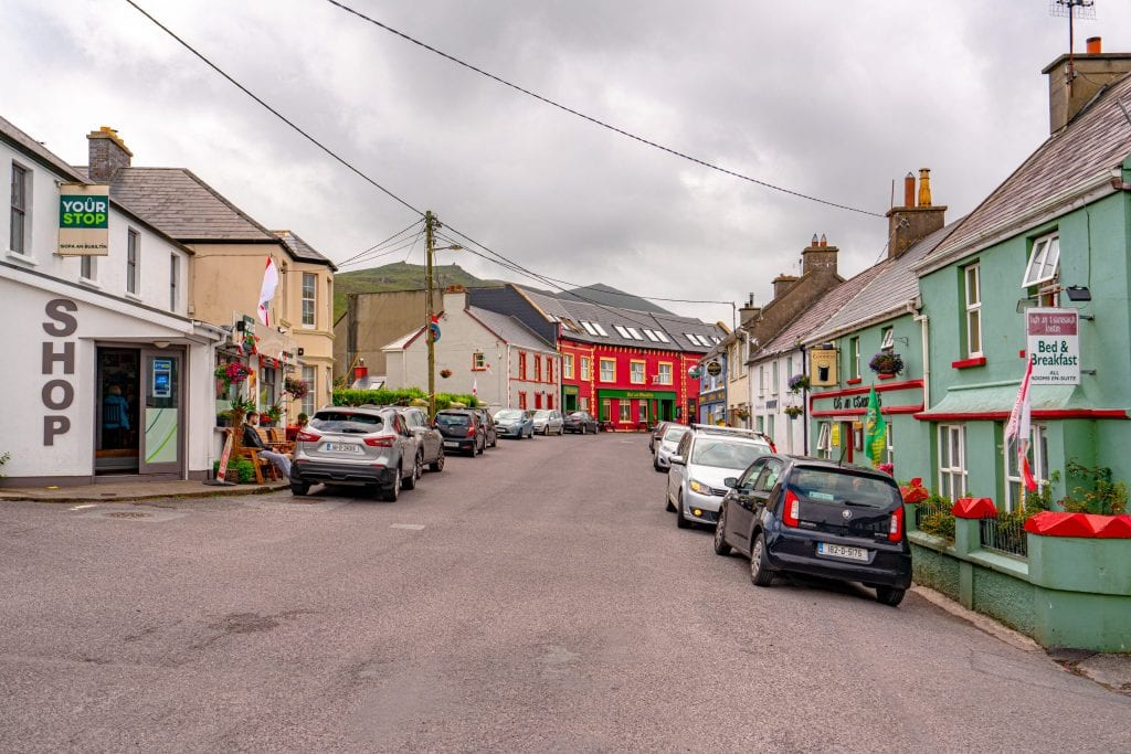 Main street in Ballyferriter Village with colorful buildings on either side and a cloudy sky