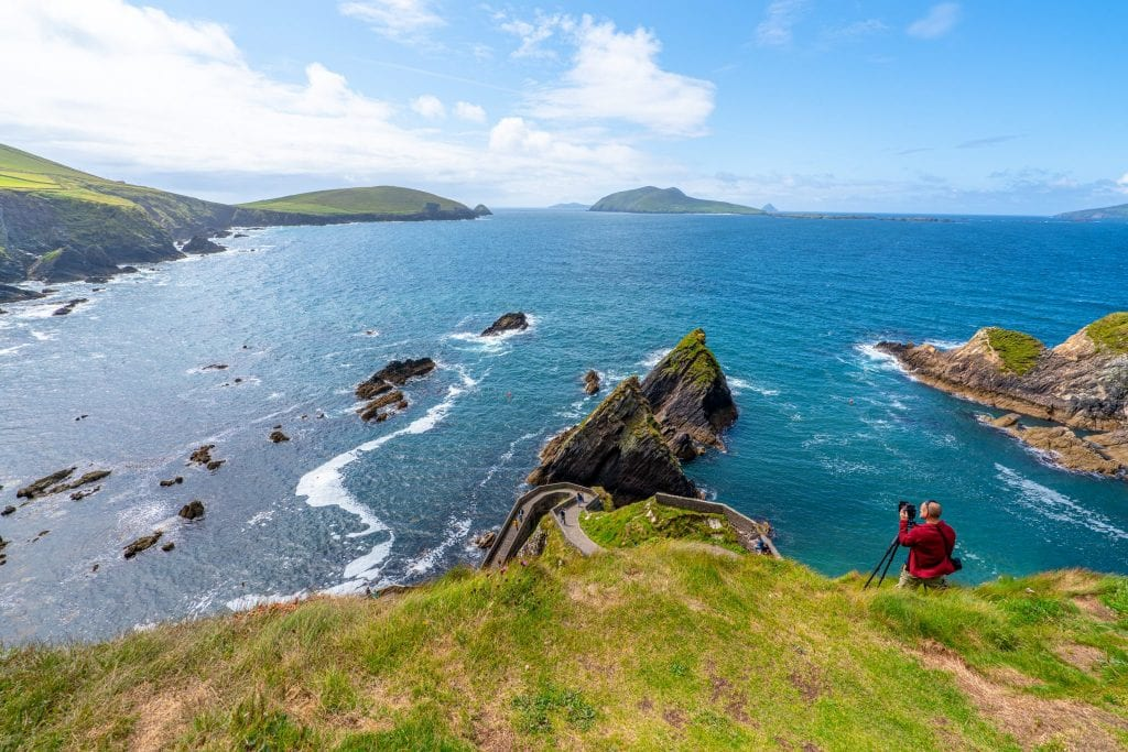 Dunquin Pier on Slea Head Drive, an unmissable place to see on a 10 days in Ireland itinerary. There's a photographer with a tripod and red jacket on the right side of the photo.