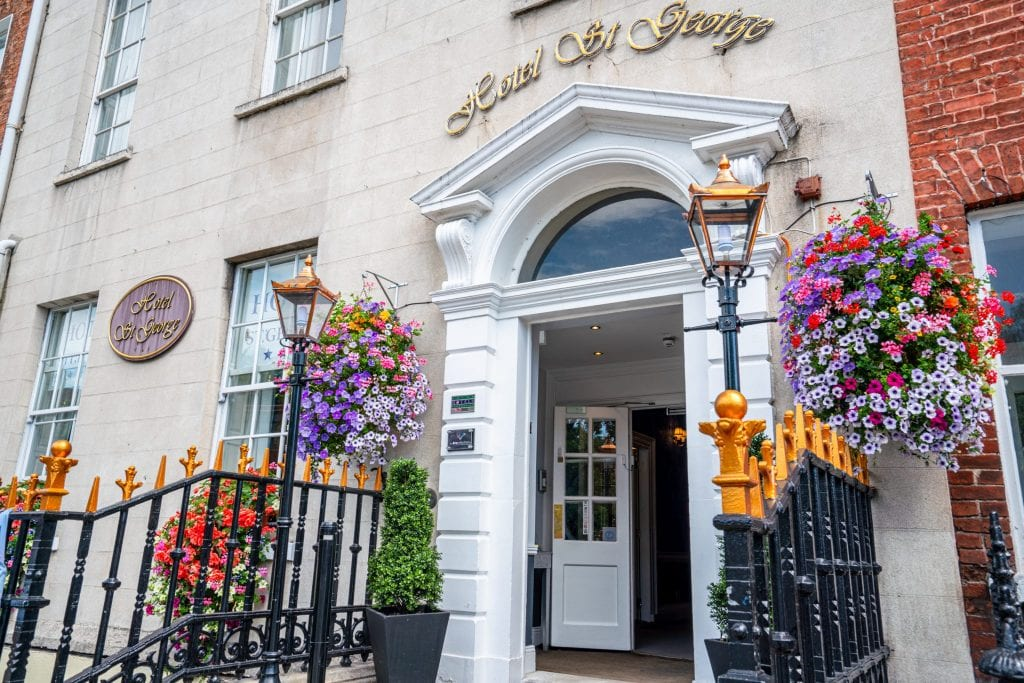Entrance to Hotel St George in Dublin Ireland. There are flowers hanging on either side of the door